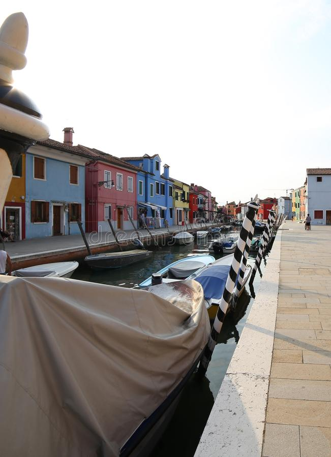 Boats moored in the navigable canal of Burano island near Venice royalty free stock photo
