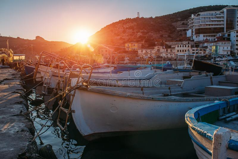Boats moored at pier in harbor in sunset light, European resort for sea vacation and rest on water transport, copy space stock image