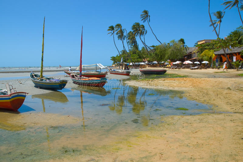 Boats moored on tropical beach stock photo
