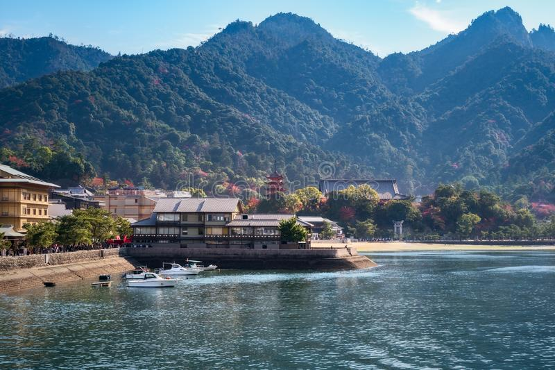 Boats near a pier at Miyajima Island in autumn in Japan. Boats near a pier at Miyajima Island in autumn with Itsukushima Shrine and Mount Misen in the stock photography