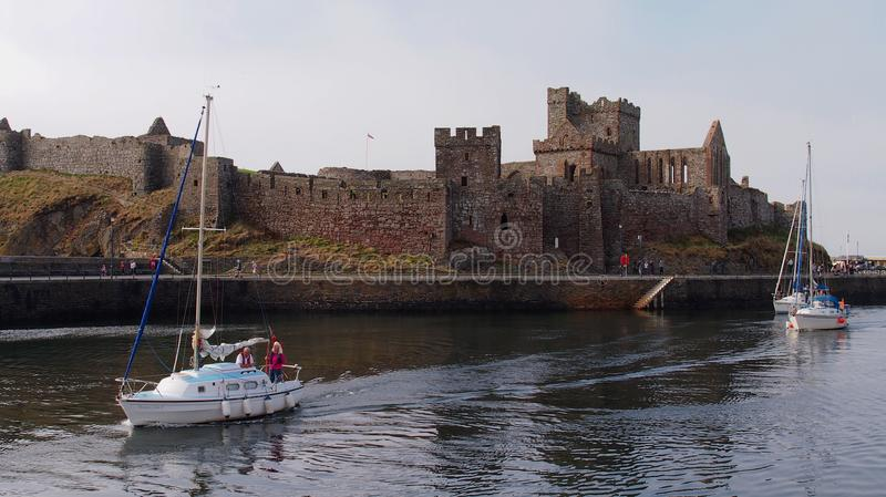 Boats passing Peel Castle on St Patrick`s Isle on the Isle of Man. Peel Castle on the Isle of Man was originally constructed by the Vikings stock photography