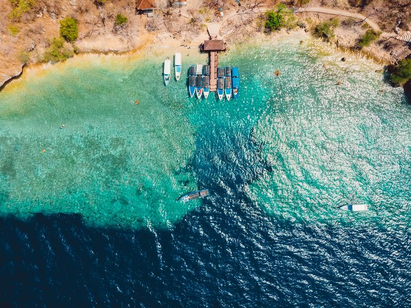 Boats at the pier in ocean on Menjangan island. Aerial view. Boats at the pier in ocean on Menjangan island royalty free stock images