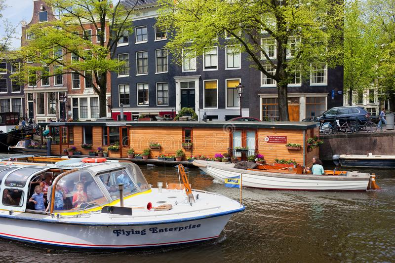 Boats on Prinsengracht Canal in Amsterdam. Amsterdam, Holland, Netherlands - May 7, 2013:  Prinsengracht Canal with cruise boat, houseboat and traditional Dutch stock image