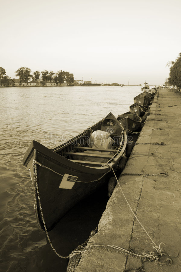 Boats on the river side. Boats tide on the river side sepia tone royalty free stock images