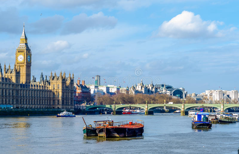 Boats on the River Thames by the iconic Big Ben. Houses of Parliament as boats sail the calm waters of the Thames in summer stock photos