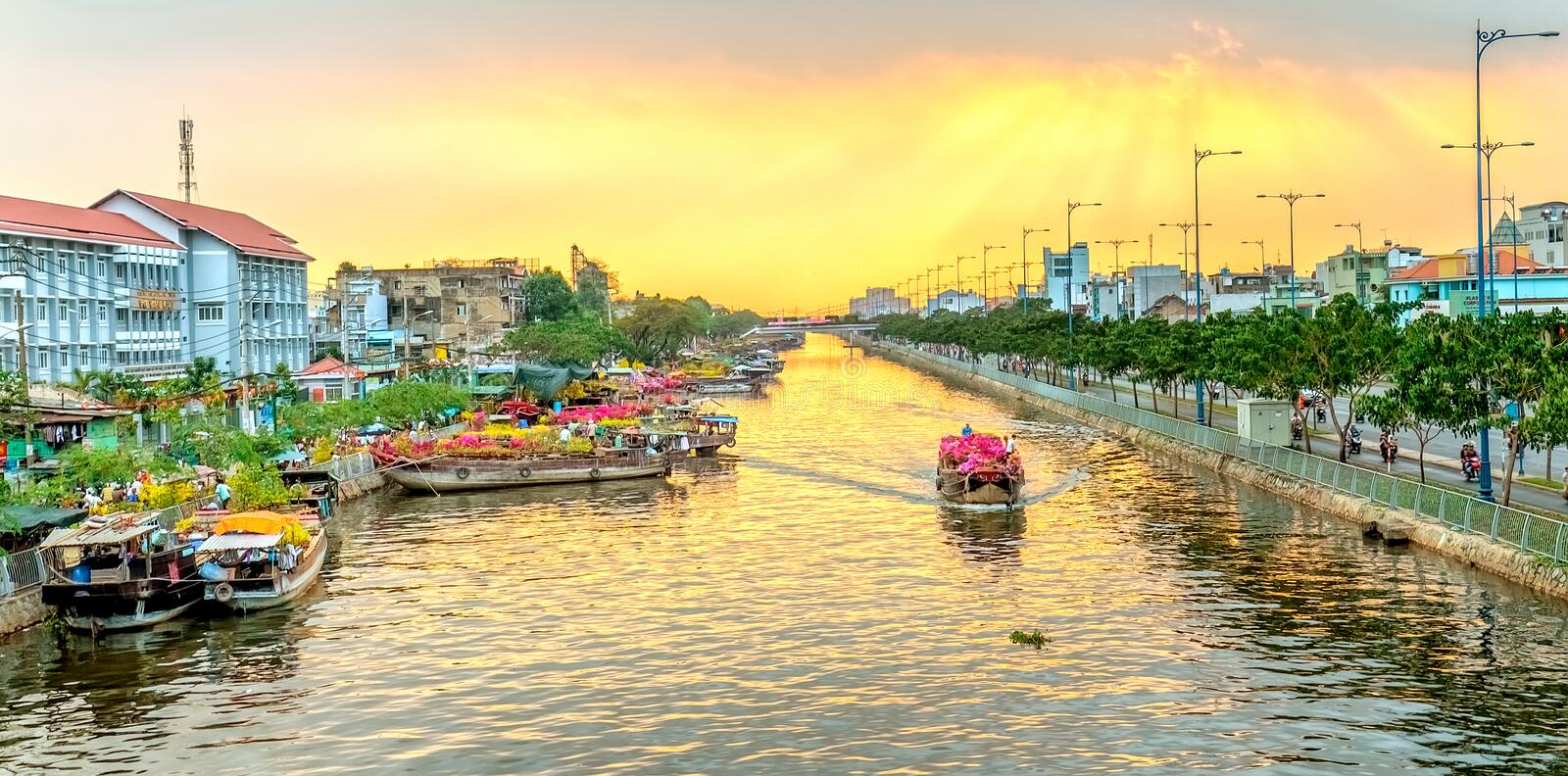 Boats on river wave flowers turn rays sunset. Ho Chi Minh City, Vietnam - February 6th, 2016: Boat on river carry flowers to sell in afternoon festival with ray stock photo