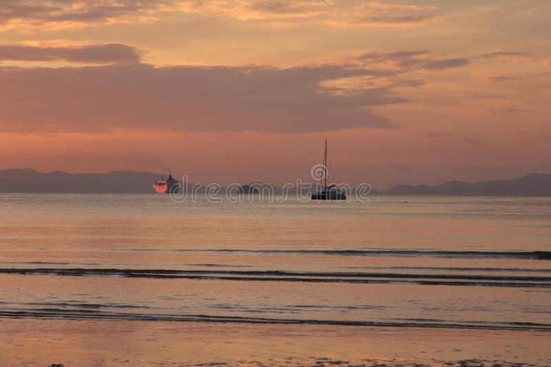 Boats sailing off to sunset stock photography