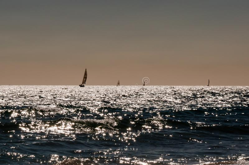 Boats sailing on Sardinia sea backlit stock image