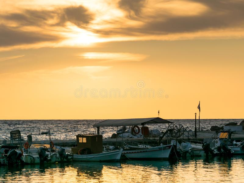 Boats sailing at the seashore at sunrise, overlooking the sea. This photo was taken at the shore of the Mediterranean Sea in Greece. The natural light of the sun stock photos