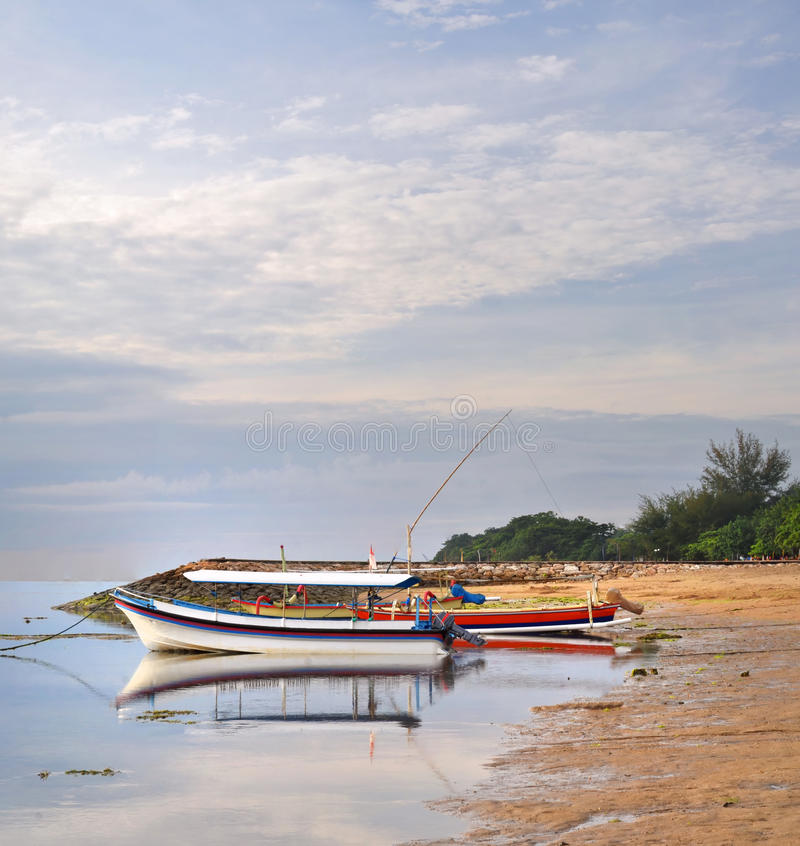 Boats on Sanur Beach at Dawn in Bali, Indonesia. stock photo