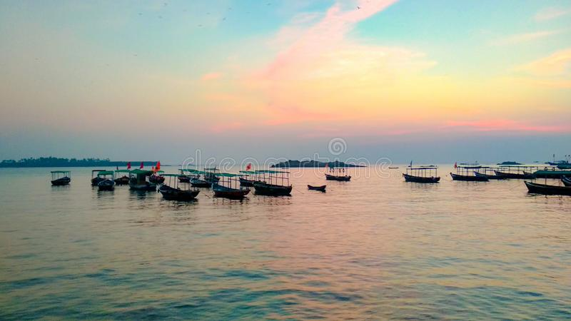 Boats in sea during sunset stock photography