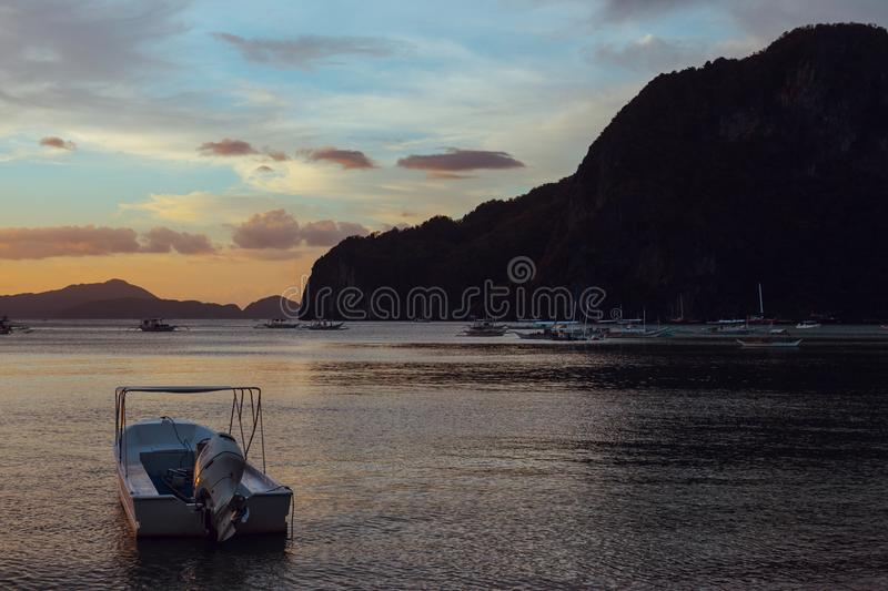 Boats in the sea at sunset. White boat on big mountain background.  Philippines isles. Fishing boat at sunset. stock photography