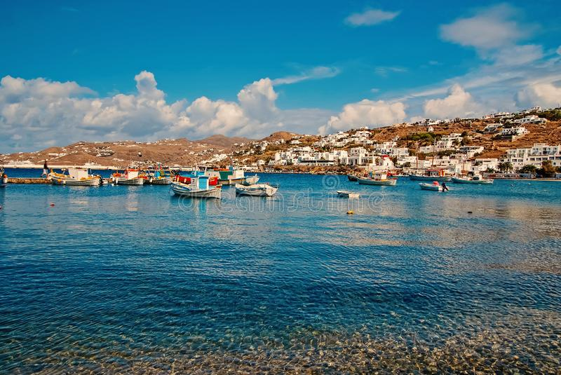 Boats on sea water in Mykonos, Greece. Sea village on cloudy blue sky. White houses on mountain landscape with nice. Architecture. Summer vacation on stock photo