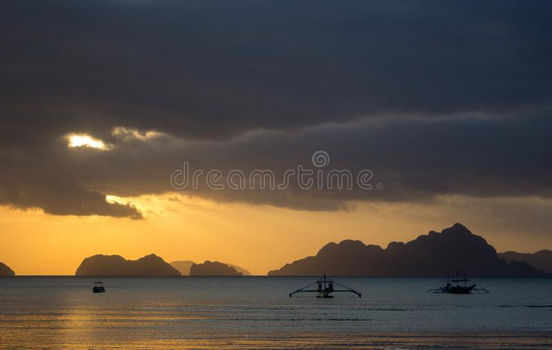 Boats silhouette in the sea on sunset and isles background. Traditional Philippines fishing boat at sunset. Scenic sunset on sea. Boats silhouette in the sea on stock photography