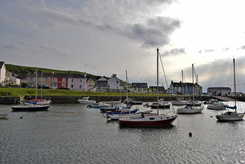 Boats moored in the harbour with the different coloured brightly coloured houses in the background in Wales. The boats, some are pleasure and some are fishing royalty free stock photography