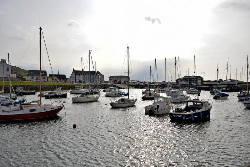 Boats moored in the harbour with the different coloured brightly coloured houses in the background in Wales. The boats, some are pleasure and some are fishing stock images