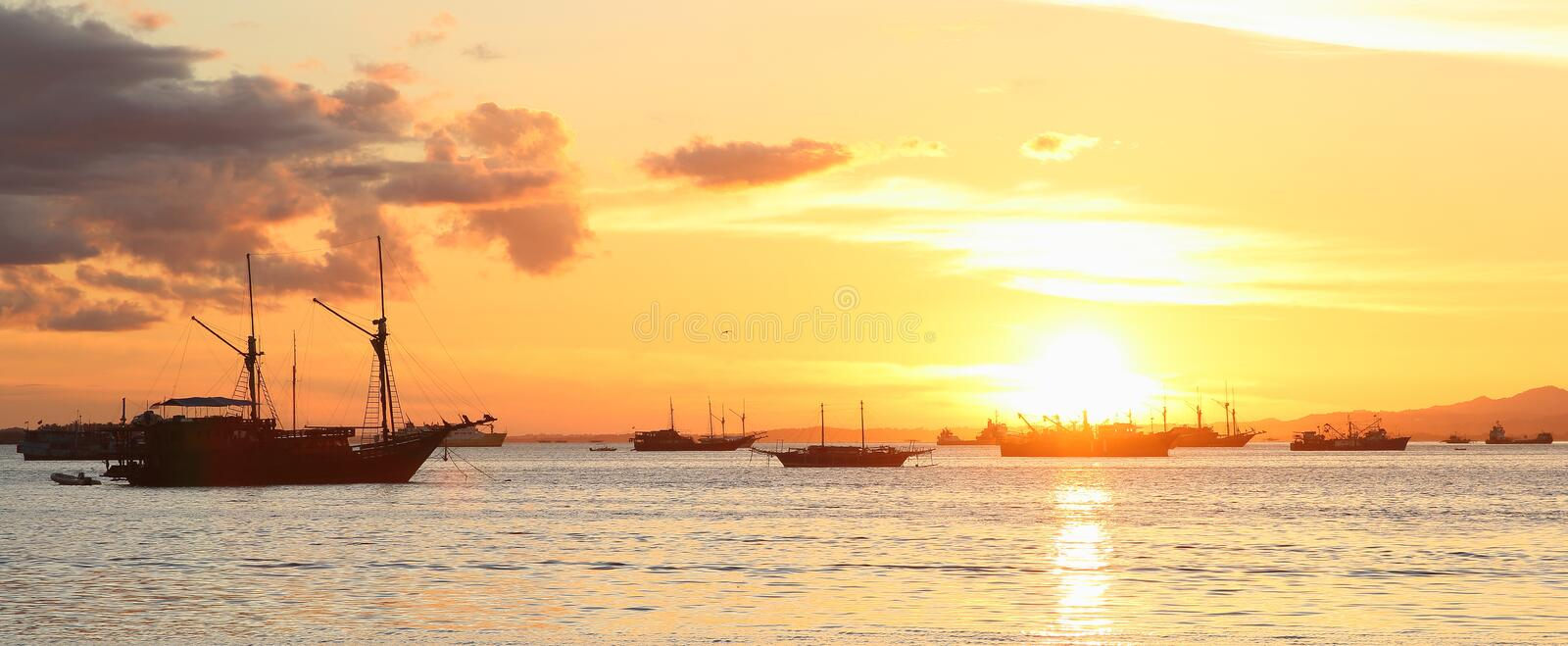 Boats on sunset sea. Boats on sea during golden sunset (Sorong, Papua Barat, Indonesia royalty free stock photo