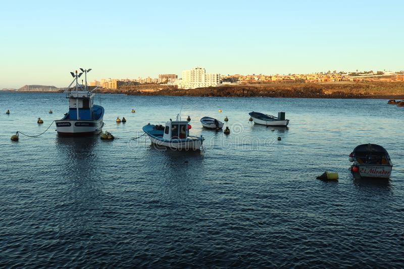 Boats on the blue water in Tenerife, Spain. Boats tied up in the harbor on an early winter morning as the rising sun starts to hit the city in the background on stock photo