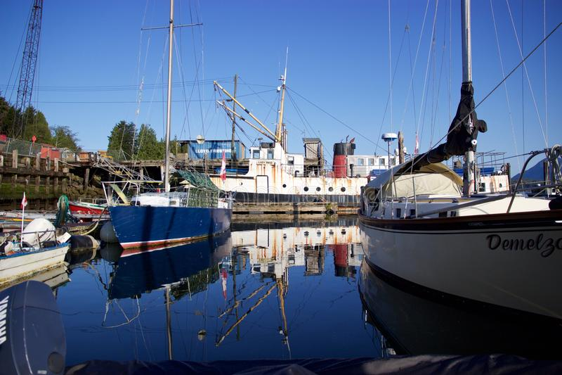 Boats in Tofino, British Columbia, Canada, reflected in harbour waters. A sunny spring day in Tofino on Vancouver Island, British Columbia, Canada. Boats in the stock image