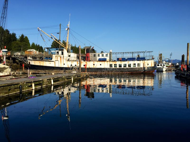 Boats in Tofino, Canada, reflected in harbour waters. A sunny spring day in Tofino on Vancouver Island, British Columbia, Canada. Boats in the harbour are stock photography