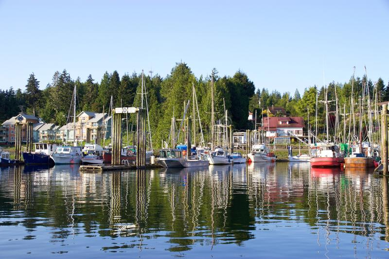 Boats and trees in Tofino, Canada, reflected in harbour waters. A sunny spring day in Tofino on Vancouver Island, British Columbia, Canada. Boats in the harbour royalty free stock photo