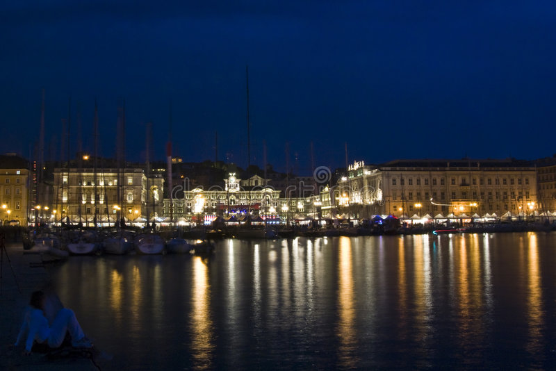 Boats in Trieste. View of Piazza Unità d'Italia from molo Audace with boats and stands during Barcolana sailboat race / event at dusk / night - (Trieste royalty free stock image