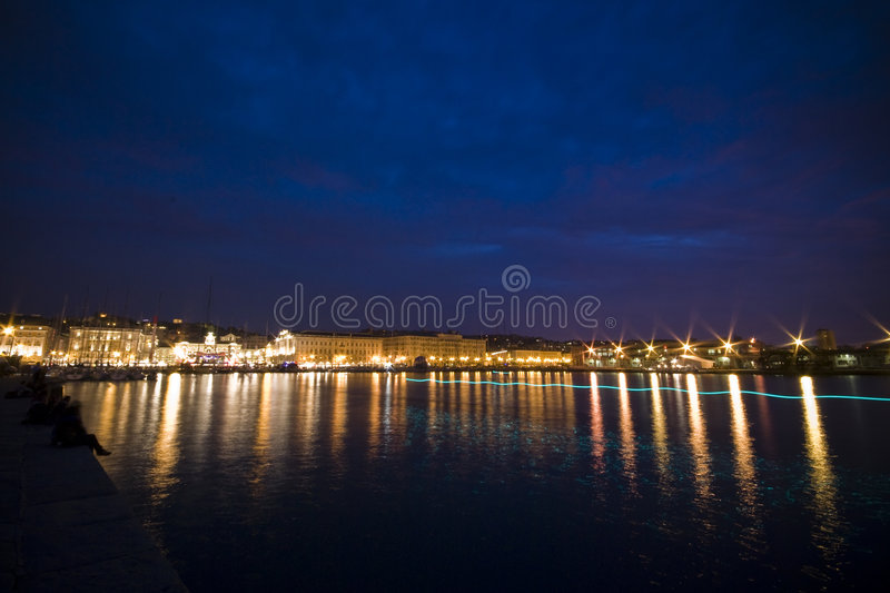 Boats in Trieste. View of Piazza Unità d'Italia from molo Audace with boats and stands during Barcolana sailboat race / event at dusk / night - (Trieste royalty free stock photography