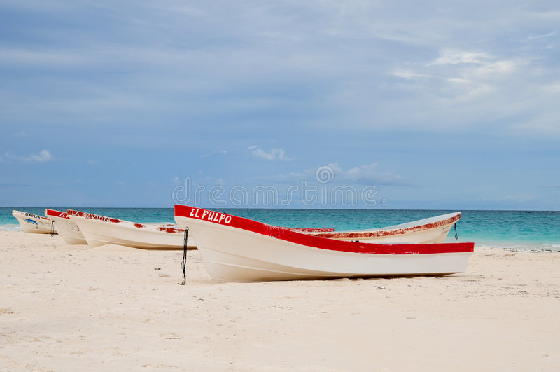Boats on tropical beach. Row of small fishing boats moored on tropical beach stock photos