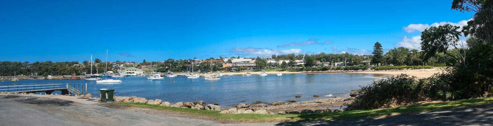 Boats on Ulladulla Harbour New South Wales. Panoramic scene of boats on Harbor with boats on calm clear blue water. Ulladulla, New South Wales, South Coast stock images