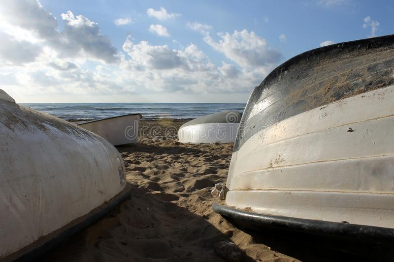 Boats upside down on the sand of the beach royalty free stock photography