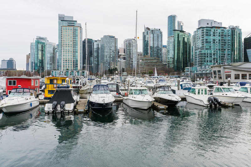 Boats and yachts with highrise buildings in Vancouver, Canada. Vancouver, Canada - January 28, 2017: Vancouver city skyline with boats in foreground stock photos