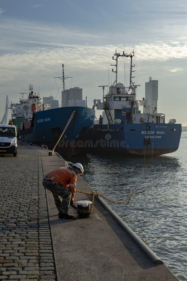 Boatsman vastmakend schip aan kade Rotterdam stock afbeelding