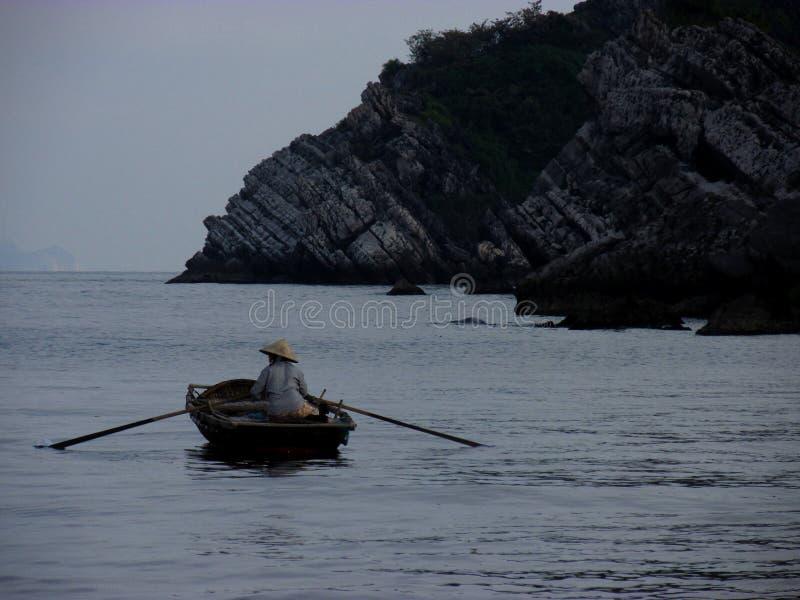 Boatwoman vietnamita solitario en el crepúsculo imagen de archivo