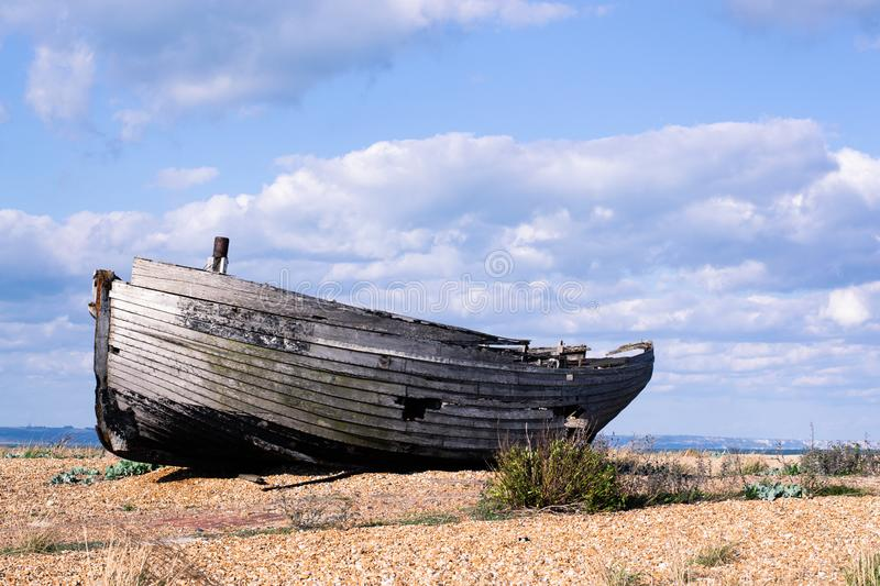 Boatwreck on a shingle beach. Abandoned wooden boat on a shingle beach on a sunny afternoon. The boat is rotting away. An impression of loneliness, nostalgia stock image