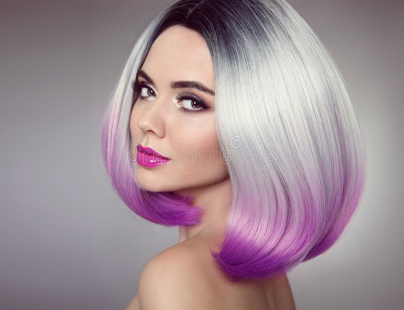 Bob hairstyle. Colored Ombre hair extensions. Beauty Model Girl. Blonde with short purple hair style isolated on gray background. Closeup woman portrait royalty free stock images