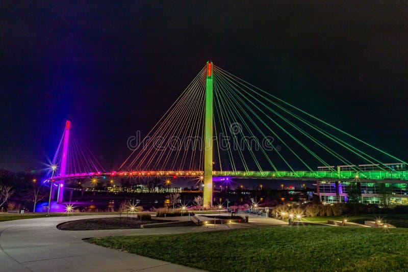 Bob Kerrey pedestrian bridge Omaha Nebraska at night with purple, yellow and green lights reflections in Missouri river. Bob Kerrey pedestrian bridge Omaha royalty free stock image