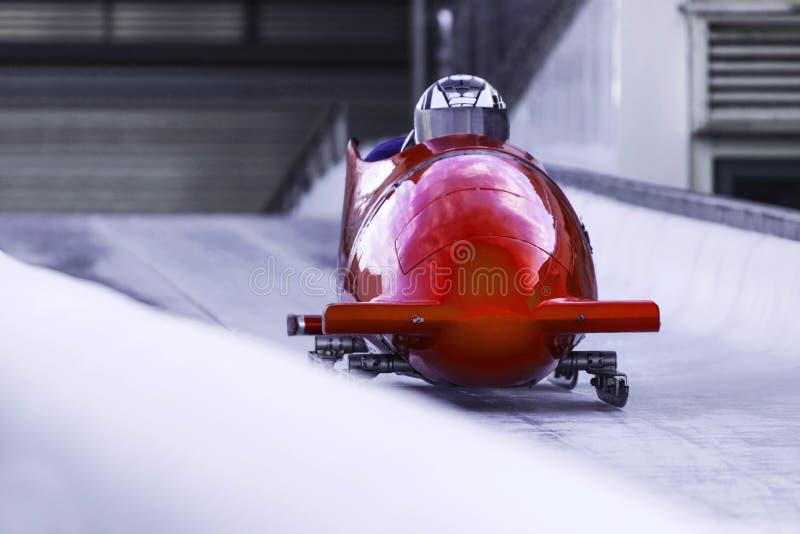 Bob sled speeding in een ijskanaal stock afbeeldingen