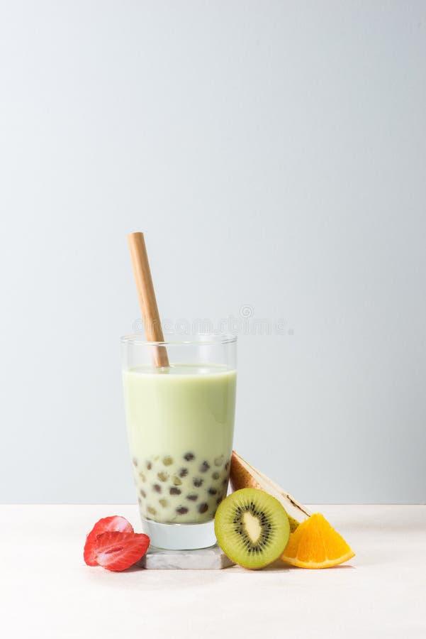 Boba/ buble tea  glass with kiwi, strawberry, orange slices on blue background royalty free stock images