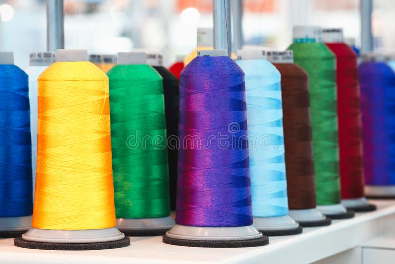 Bobbins with colored thread for industrial textile machines.  stock photo