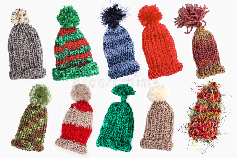 Bobble caps for winter. Eight knitted warm bobble caps, isolated royalty free stock photos