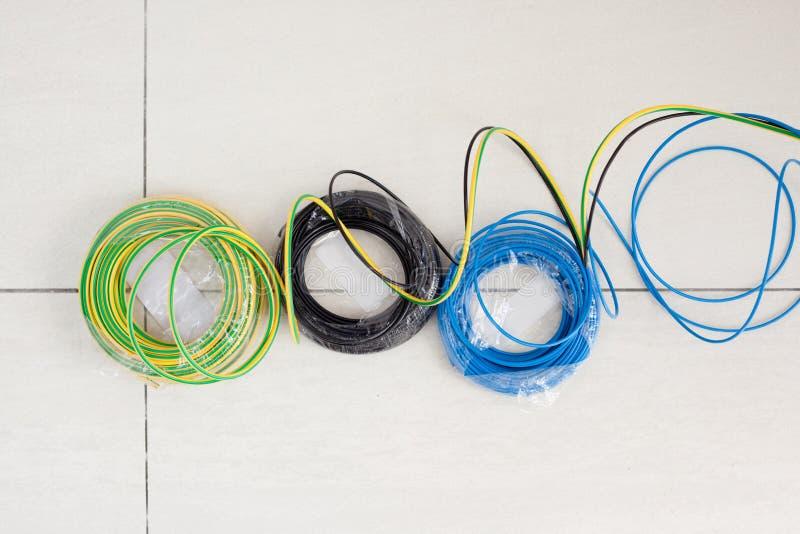 A bobina de cabo elétrico em três cores enegrece o azul e a terra foto de stock