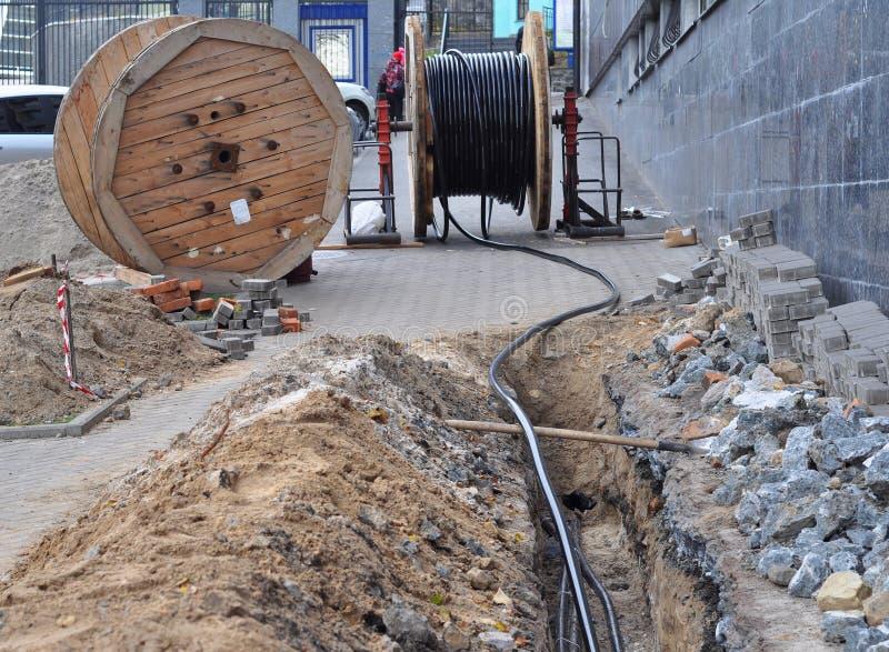 Bobina de madeira do cabo bonde e das fibras óticas na escavação na rua imagens de stock royalty free