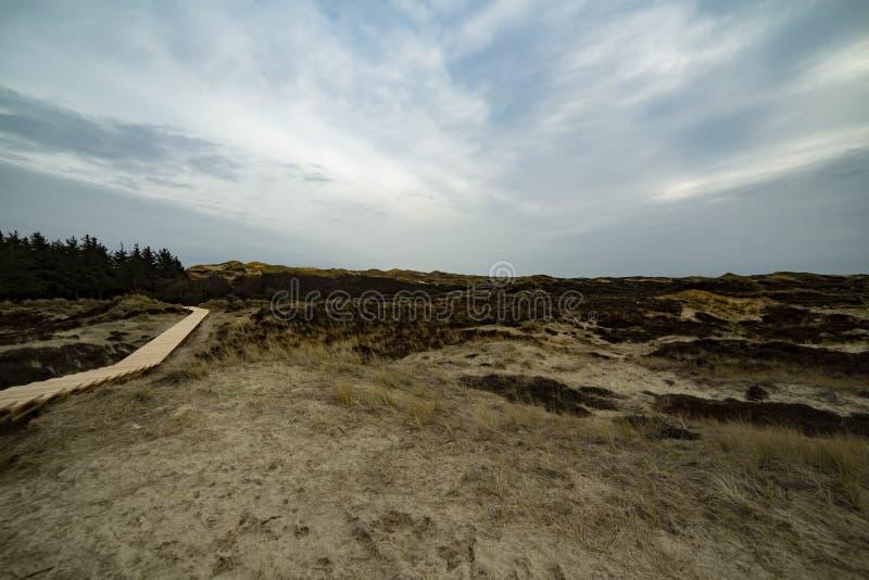 Bobina de madera del paseo mar?timo alrededor de las colinas en la l?nea de la playa fotos de archivo