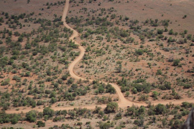 Bobina della strada non asfaltata attraverso il paesaggio arido immagine stock