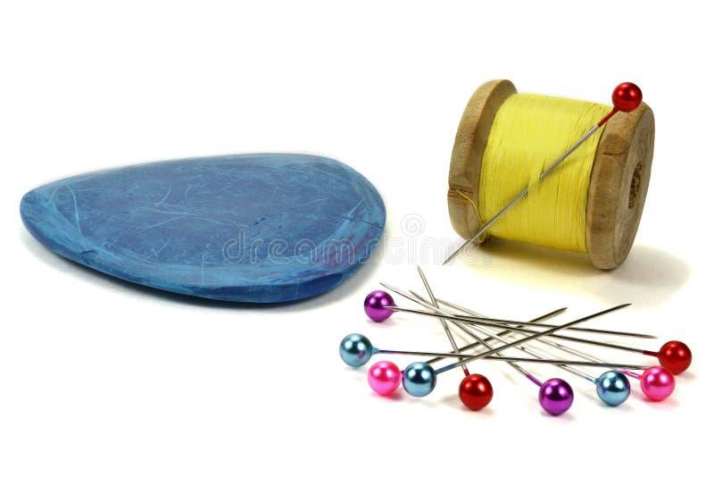 Bobina di legno con i fili, l'ago, il gesso blu ed i perni per il cucito su un fondo bianco immagini stock