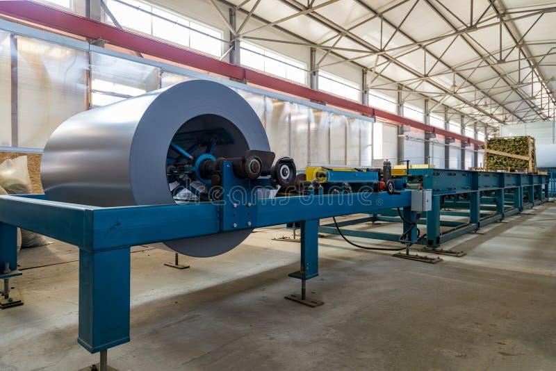 Bobina industrial da folha de metal no perfil da folha de metal que forma a máquina na oficina imagens de stock royalty free