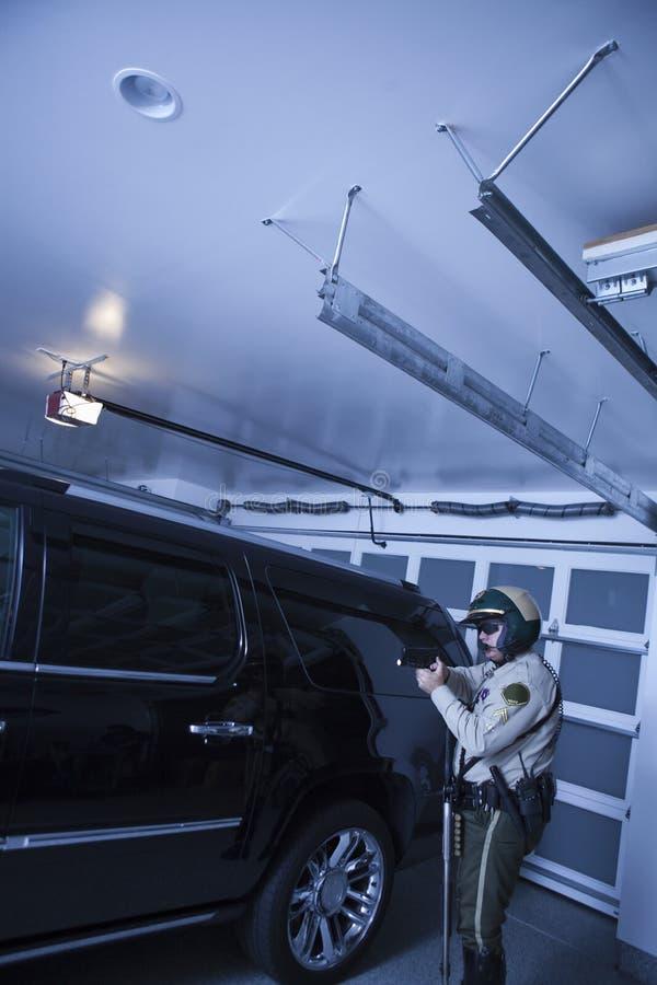 Bobina que aponta o revólver ao estar pelo carro na garagem fotografia de stock royalty free