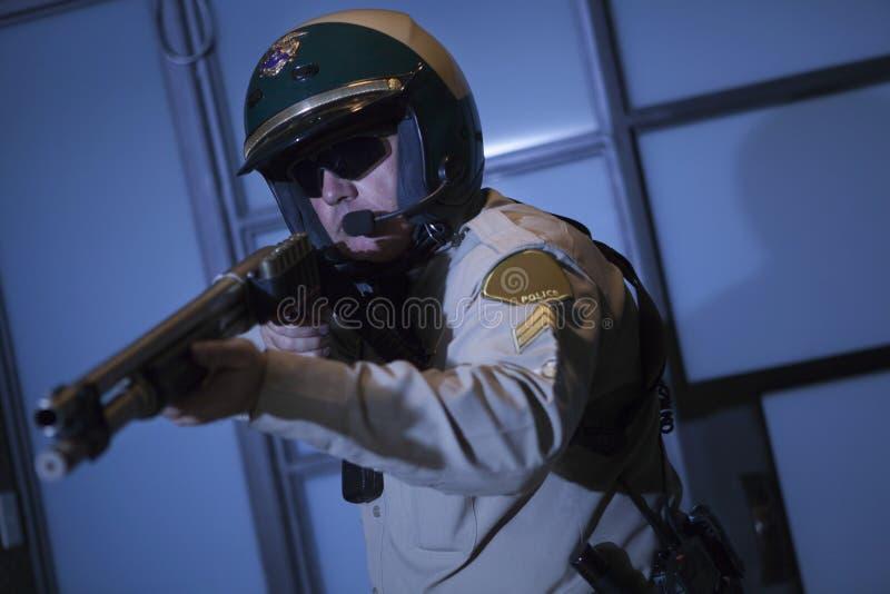 Bobina que aponta o rifle contra a porta imagens de stock