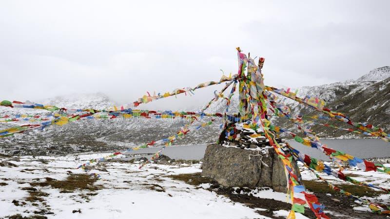 Bobinadores de cintas en modo continuo y lago de Sutra debajo de la montaña de la nieve foto de archivo