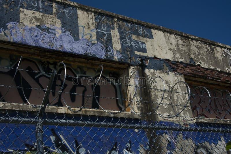 Bobinas abandonadas da construção e do arame farpado de Graffitied em Sunny Day foto de stock royalty free